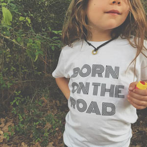a young traveling boy wearing a t-shirt that reads Born on the Road