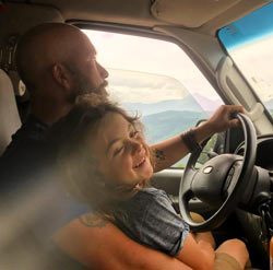 a dad drives a van while his son sits on his lap
