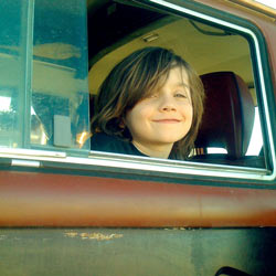 a young man smiling through a VW Bus window