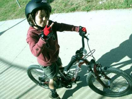 a young boy on his bike throwing up the peace sign with his fingers