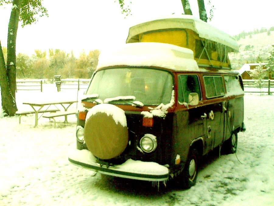 a vw bus covered in snow