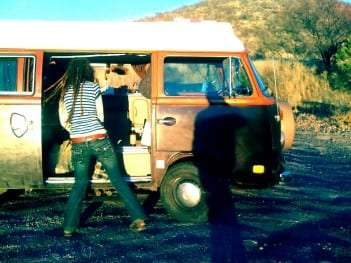 a dreadlock girl dancing outside of a vw bus near tombstone arizona
