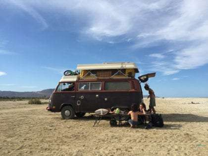 a family doing schoolwork outside of a vw bus while mom packs up the back