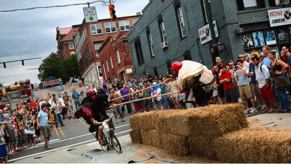 Two guys jousting on bicycles, separated by hay bails on Lexington Avenue and surrounded by spectators