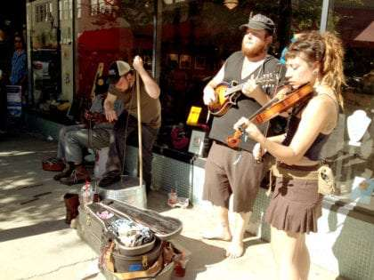 young men and a girl dressed in somewhat rag tag clothing, playing instruments on the sidewalk with a guitar case in front of them to collect tips