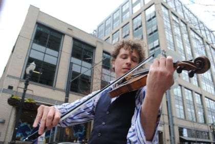 Janssen Kuhn wearing a blue & white striped shirt, vest and playing his fiddle in downtown Portland.