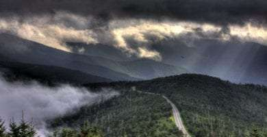 The Blue Ridge Parkway winds through the mountains on a cloudy day, as seen from Mt. Mitchell
