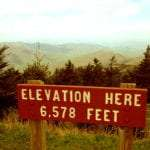 sign on mount mitchell reading Elevation Here 6,578 Feet