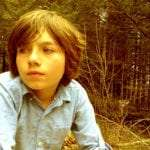 Tristan, a 10 year old boy wearing a blue shirt, with shaggy brown hair and blue eyes, in the forest