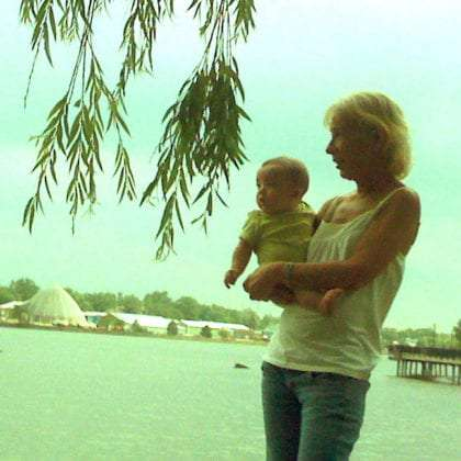 a woman holds a baby on the shores of Lake Huron