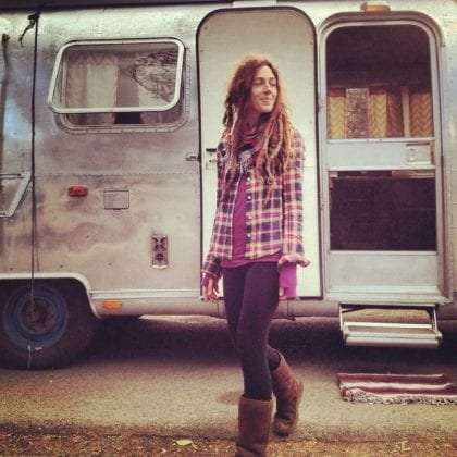a fabulously beautiful woman stands in front of a vintage airstream