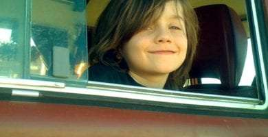 My son Tristan, long haired and hanging out the window of our 1978 VW Bus