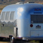 an Airstream travel trailer, shiny, silver, and vintage