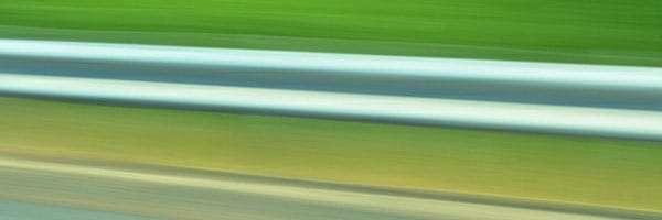 the blur of a freeway guard rail
