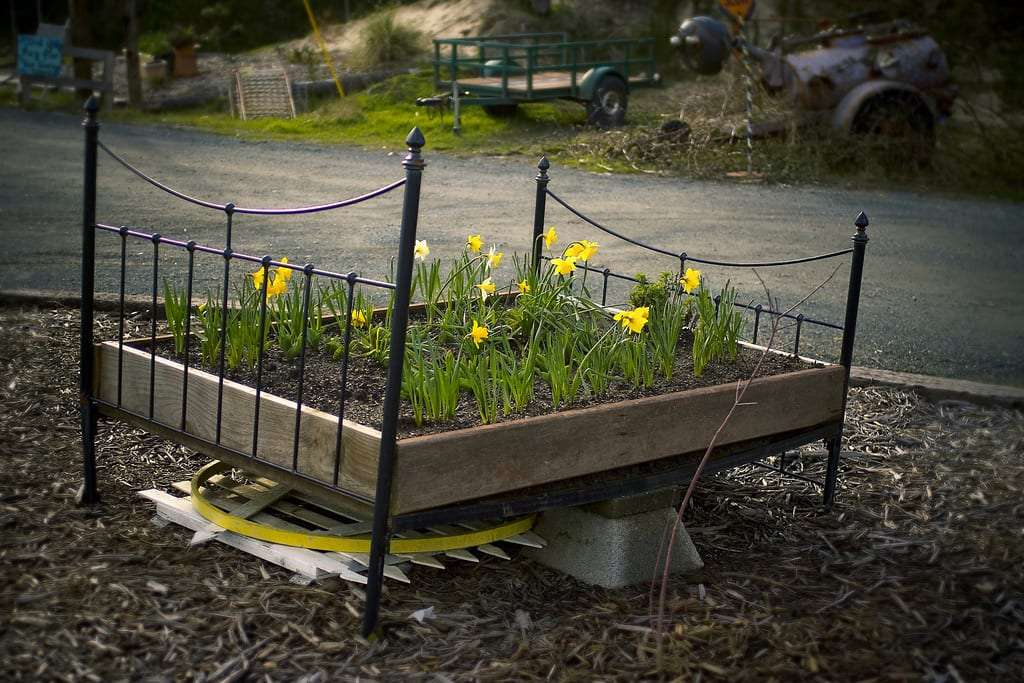 a flower bed made from an old bed frame