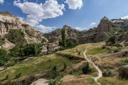 the expansive landscape of Cappadocia's pigeon valley, peaking mountain, blue sky and a trail through rolling hills