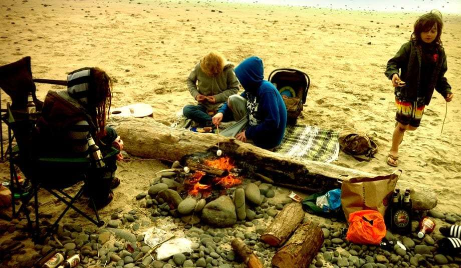 a family sitting around a fire cooking s'mores on Oregon's Indian Beach in Ecola State Park