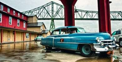an old but very well maintained Cadillac sits in front of Cannery Pier Hotel, the Astoria-Megler Bridge in the background.