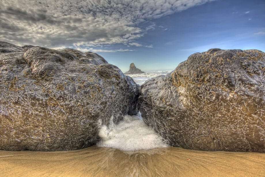 Waves crash between two boulders on Indian Beach, Ecola State Park, Oregon