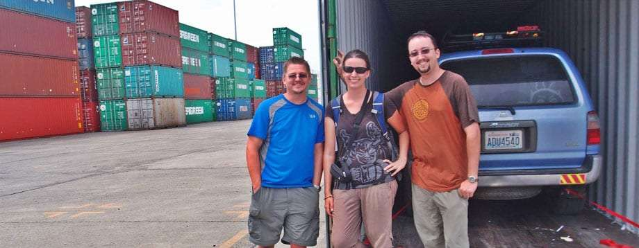 three young people in a shipping freight yard, there blue 1997 Toyota 4Runner in the background