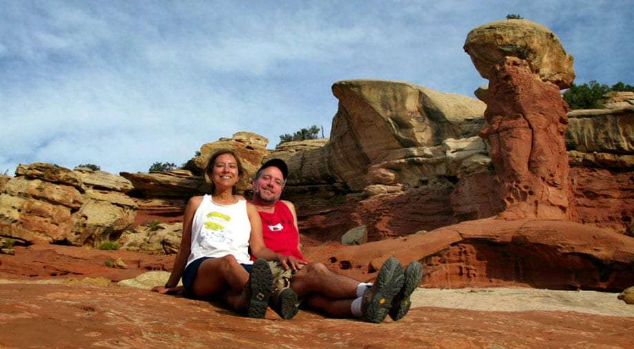 Jim Nelson and René Agredano sitting on the red rocks of Utah's National Parks.