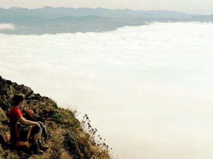 A hiker sits atop Neah-Kah-Nie Mountain, fog below him, mountains layered in the distance