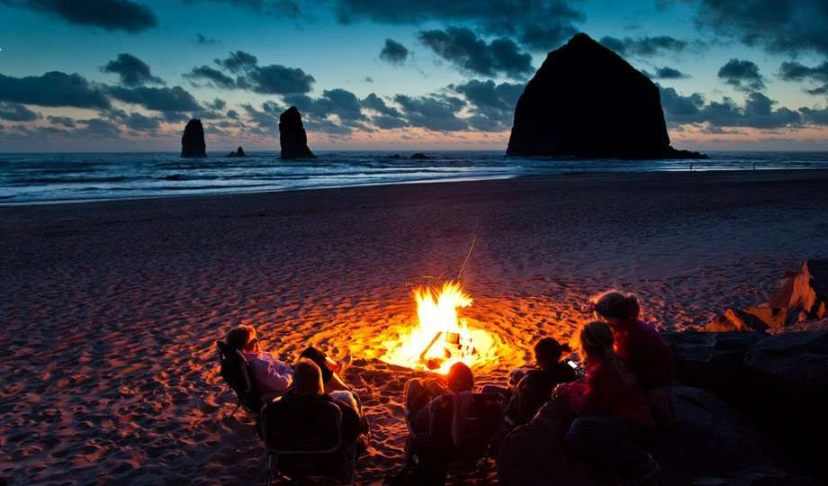 several people enjoying a beach fire near Haystack in Cannon Beach, OR