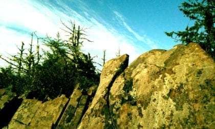 rock outcrop set against evergreens and a partly cloudy Oregon sky