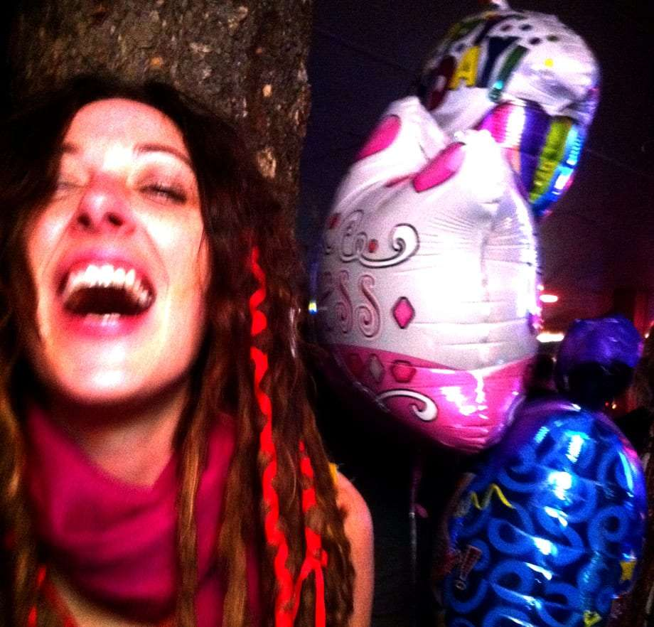 a woman laughs heartily while standing by three balloons at the Lighthouse