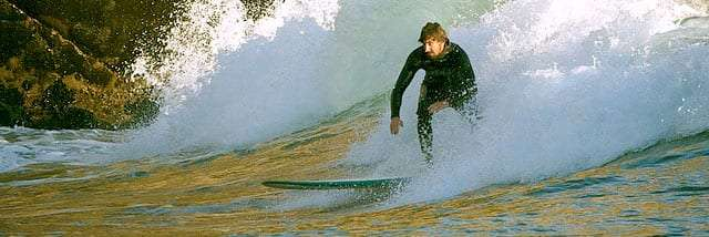 a surfer rips it up as the waves crash dangerously close to some rocks