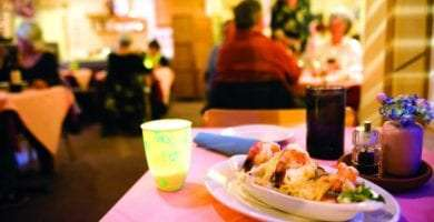 a shrimp dinner on display, sitting on table with a pink table cloth, blurred out patrons and the owner/waiter in the background