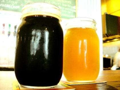 two mason jars, one filled with the nearly black Cavatica Stout, the other with honey colored Vortex IPA