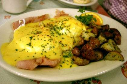 a plate of egg's benedict, eggs smothered in hollandaise sauce, ham, homestyle potatoes and an orange