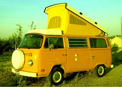 a yellow 1977 Volkswagen Bus with the Westfalia pop top up, in a grassy field against the blue sky