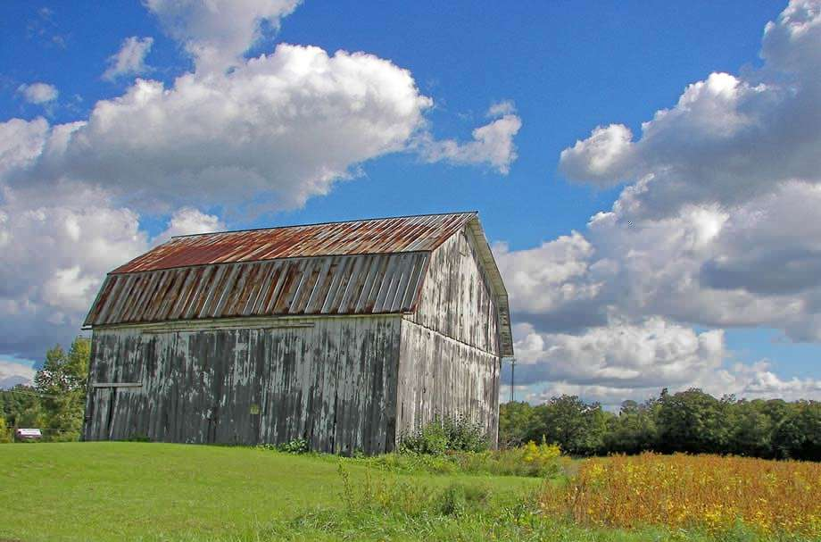 a gray barn with a slightly rusted roof which is tilted as though ready to fall in a green field against a partly cloudy sky