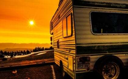 the sun sets near Crater Lake, an older RV in the foreground. Photograph by Ben Willmore.