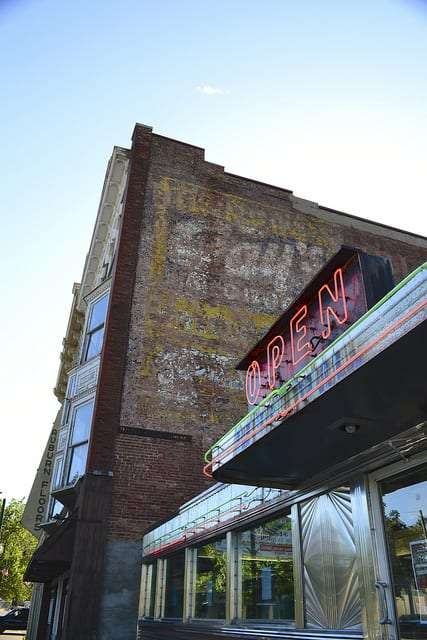 a neon Open sign against a faded painted sign on a brick building