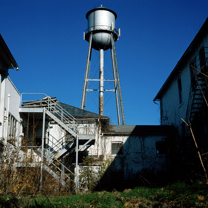 an old water tower in a seemingly abandoned warehouse or farm