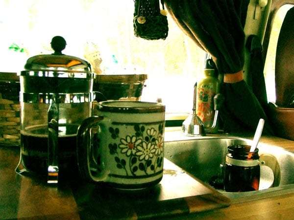 a french press half full of coffee, a mug and a cup in the sink of a volkswagen bus