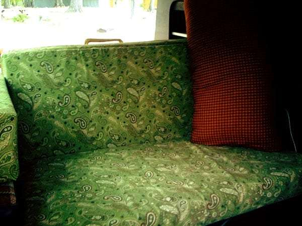 a paisley green couch with an orange pillow