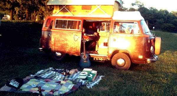 a blanket laid out in the grass in front of a vw bus