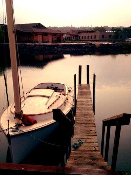 a sailboat docked in the waterways, the city of Ithaca in the distance behind