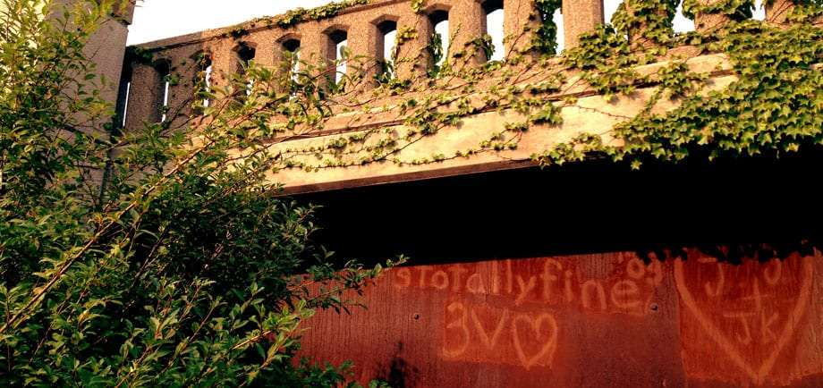 a rusted, ivy covered bridge with fading graffiti