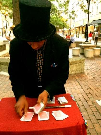 a magician in a black suit performs card tricks in ithaca commons