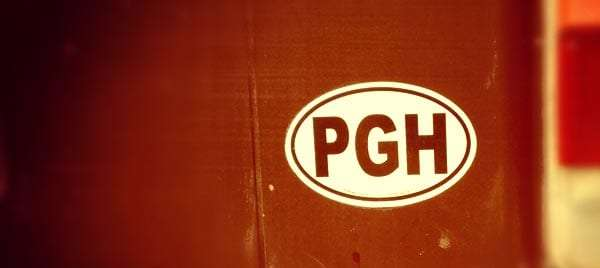 a circular white sticker with the letters PGH on it, stuck to the back of a VW Bus near the tail light