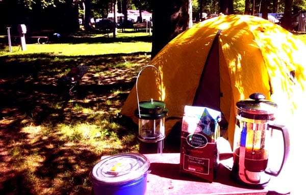 a yellow tent set up behind a picnic table with a lantern and some coffee making supplies