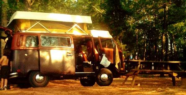 a brown volkswagen bus with the camper top popped up sitting in a wooden area