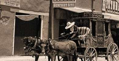 sepia toned photograph of man driving stage coach underneath the OK Corral sign in Tombstone, Arizona