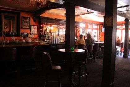 a dimly lit bar, few patrons, antique architecture abounds