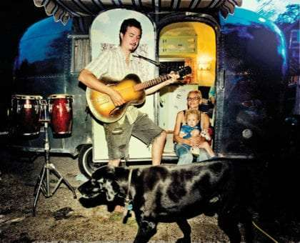 a man plays guitar while a woman holding a baby sits in the doorway of an Airstream, a black dog walks in front of them all.